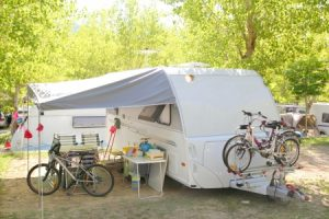 8289240 - camping camper caravan trees park with bicycles